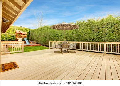 Spacious wooden deck with umbrella and patio table set. View of play yard with chute
