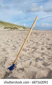 spade standing upright in sand on beach