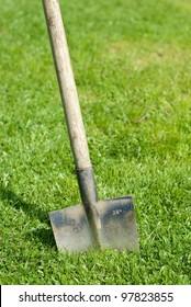 a spade stuck in the grass