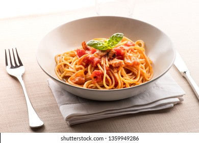 Spaghetti all' amatriciana from the Lazio region of Italy with pecorino cheese, pepper, tomato, cured pork jowl or guanciale served in a bowl as a first course to Italian cuisine