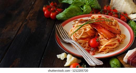 Spaghetti alla amatriciana on a wooden table close up