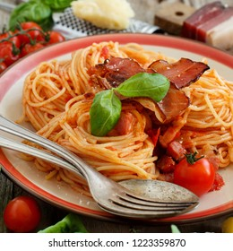 Spaghetti alla amatriciana on a wooden table close up