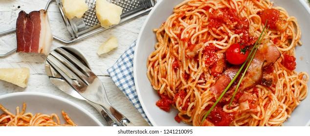 Spaghetti alla amatriciana on a wooden table top view