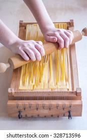 Spaghetti alla chitarra -  italian fresh egg pasta specialty of Abruzzo region with tools to make it