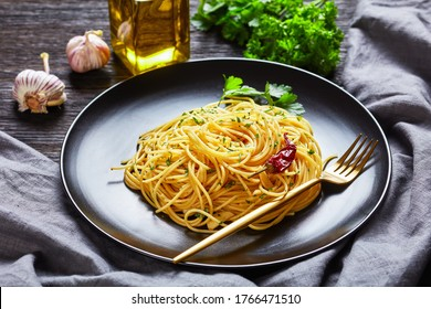 Spaghetti Alla colatura di alici, Spaghetti tossed with anchovy sauce, pimento pepper, garlic and parsley on a black plate with golden fork on a dark wooden table, landscape view
