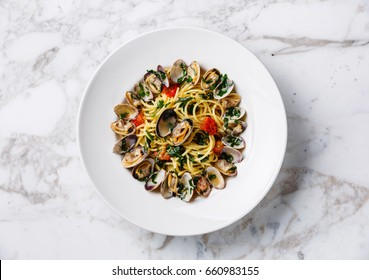 Spaghetti alle Vongole Clams pasta with tomato and parsley on white marble table