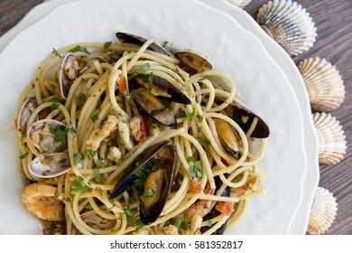 Spaghetti allo scoglio, pasta with seafood in white ceramic plate on wooden background