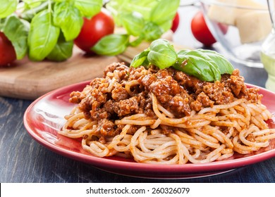 Spaghetti bolognese with cheese and basil on a plate