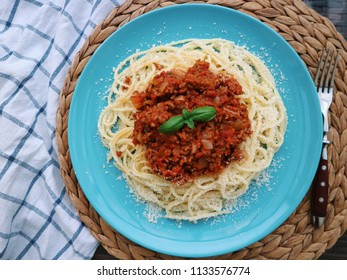 Spaghetti bolognese with fresh basil and Parmesan cheese. Italian cuisine concept. Delicious spaghetti with meat and tomato sauce on a plate, wooden background. Top view