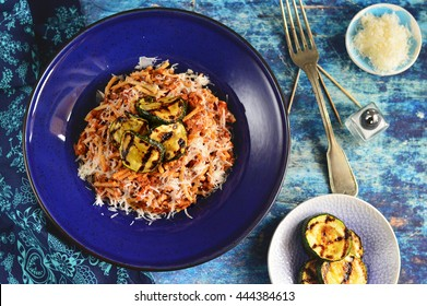 Spaghetti Bolognese with grilled zucchini slices on the top on blue plate and blue wooden table