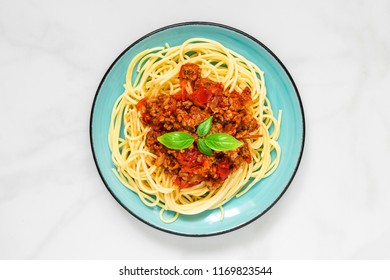Spaghetti bolognese on a blue plate on white marble table. healthy food. top view. italian pasta