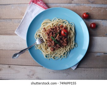Spaghetti bolognese on a colorful glossy plate. Pasta with minced meat, tomato sauce, fresh cherry tomatoes on a wooden background. Linen tablecloth. Top view.