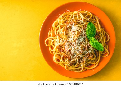 Spaghetti Bolognese on the orange plate on the yellow background top view
