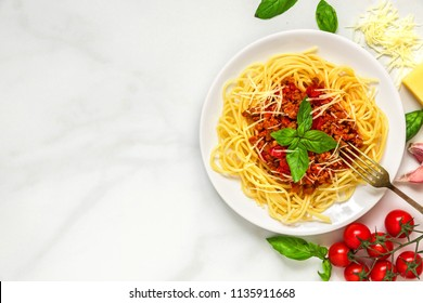 Spaghetti bolognese on a white plate with fork on white marble table. healthy food. top view with copy space