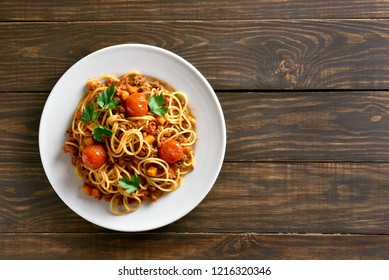 Spaghetti bolognese on white plate over wooden background with copy space. Top view, flat lay