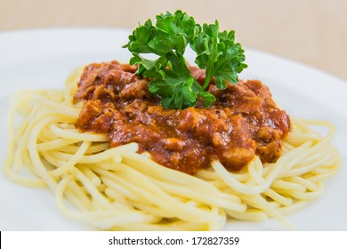 Spaghetti Bolognese on white plate, wooden table