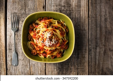 Spaghetti bolognese with parmesan cheese on rustic table