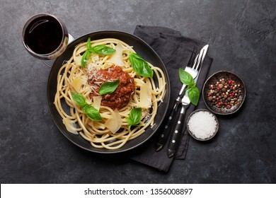 Spaghetti bolognese pasta with tomato and minced meat sauce, parmesan cheese and fresh basil. Red wine glass and cooking ingredients. Top view