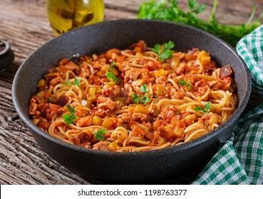 Spaghetti bolognese pasta with tomato sauce, vegetables and minced meat - homemade healthy italian pasta on rustic wooden background.