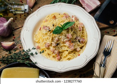 Spaghetti Carbonara. Pasta alla carbonara with a cream sauce, bacon and pepper on a white plate. Old wooden background