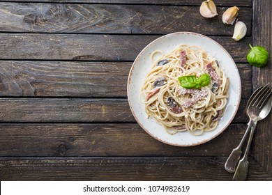 Spaghetti carbonara pasta over wooden background, top view