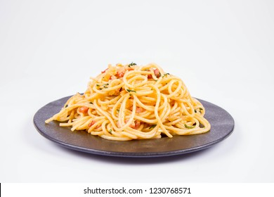 Spaghetti Carbonara with some parsley on a black plate on a white background