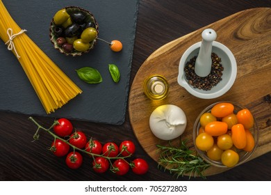Spaghetti, cherry tomatoes, olive oil, olives,  herb and spices, Burrata on old wooden background.