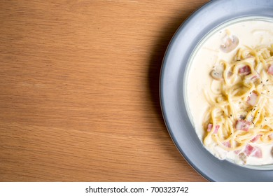 Spaghetti cream sauce and ham on the blue dish on top view with brown wooden table