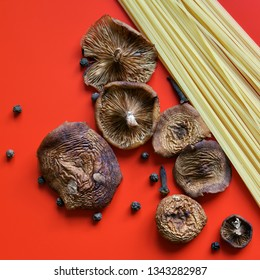 Spaghetti, dried wild mushrooms, pepper and cloves on a red background