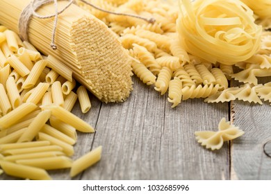 Spaghetti, farfalle, fusilli and tortiglioni lie on an old wooden table. Space for text.