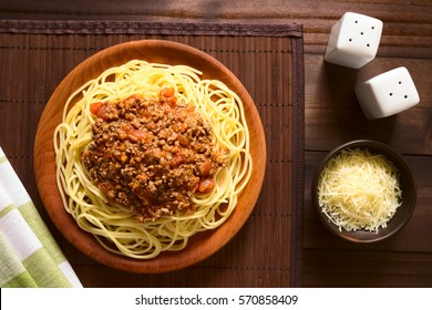 Spaghetti with homemade bolognese sauce made of fresh tomato, mincemeat, onion, garlic and carrot, grated cheese on the side, photographed overhead with natural light (Selective Focus on the sauce)