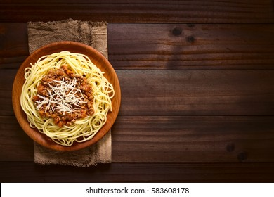 Spaghetti with homemade bolognese sauce made of fresh tomato, mincemeat, onion, garlic, carrot, served on wooden plate with grated cheese on top, photographed overhead on dark wood with natural light