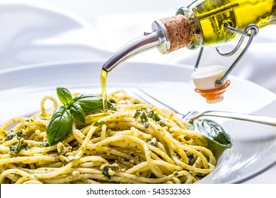 Spaghetti with homemade pesto sauce pouring olive oil and basil leaves.