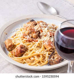 Spaghetti with homemade sausages and eggplant sprinkled with grated cheese in a plate and a glass of red wine in the foreground, selective focus - traditional Italian rural lunch