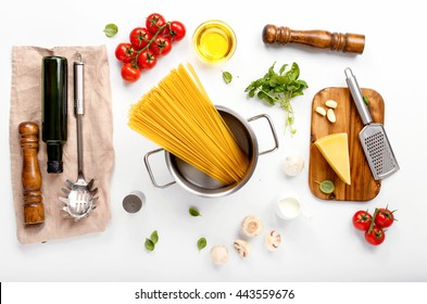 Spaghetti with ingredients for cooking pasta on a white background, top view