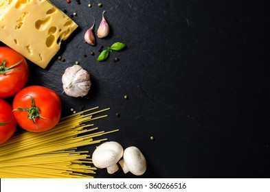 Spaghetti ingredients over dark background