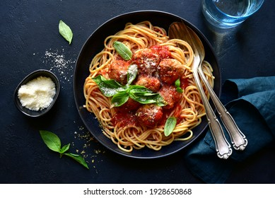 Spaghetti with meat balls in tomato sauce in a black bowl on a dark slate, stone or concrete background. Top view with copy space.