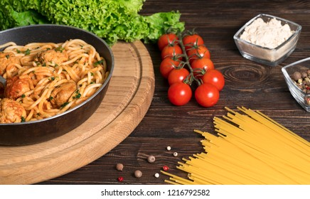 spaghetti with meat and tomatoes on a wooden background