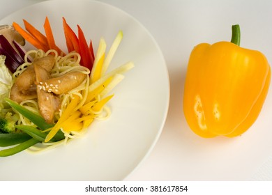 Spaghetti with meat, vegetables and sesameon white plate closeup isolated on white