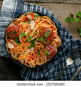 Spaghetti with meatballs, parmesan and tomato sauce in a bowl on a rustic wooden table. Tasty Italian pasta food. Top view shot.