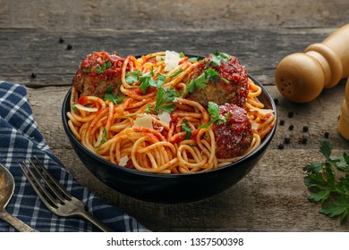 Spaghetti with meatballs, parmesan and tomato sauce in a bowl on a rustic wooden table. Tasty Italian pasta food.