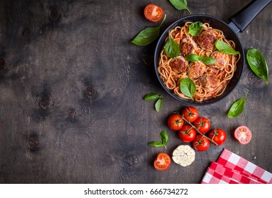 Spaghetti with meatballs, tomato sauce. Background. Italian American dish. Meatballs pasta in a pan. Space for text. Overhead. Traditional Italian cuisine. Dark rustic wooden table. Dinner with pasta