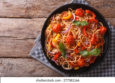 Spaghetti with minced meat and vegetables. horizontal top view, rustic style