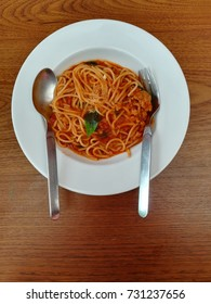 Spaghetti minced pork with tomato sauce in white plate on wooden table.