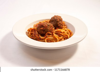 spaghetti noodles in marinara sauce topped with meatballs and in white bowl