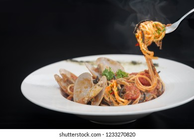 Spaghetti on a fork and smoke or hot steam. Delicious linguine pasta in a clams sauce close up and herbs on black background.copy spaced