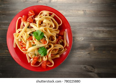 spaghetti on a plate. spaghetti tomatoes, onions, cabbage on a wooden background