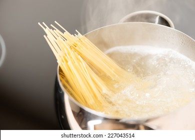 Spaghetti in pan cooking in boiling water