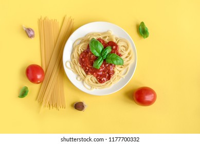 Spaghetti pasta bolognese and ingredients on yellow background, top view. Plate of pasta dish with tomato sauce and basil on creative yellow background.