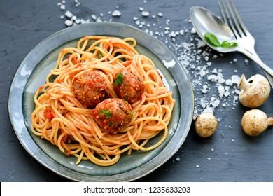 Spaghetti pasta Italian home made meal. Mediterranean food concept . Fresh Spaghetti pasta meatballs with tomato sauce, basil, herbs ,parmesan cheese